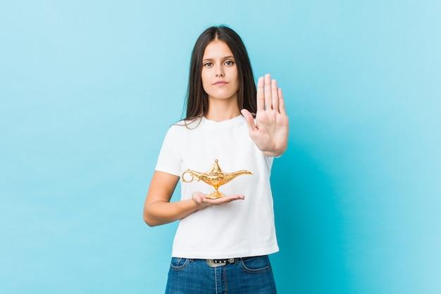 Młoda kobieta trzyma magiczną lampową pozycję z szeroko rozpościerać ręką pokazuje znak stop, zapobieganie ci