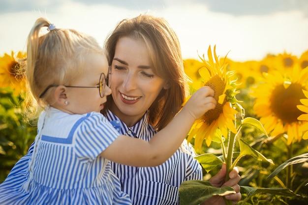 Młoda kobieta trzyma małą dziewczynkę w ramionach na słonecznikowym polu.