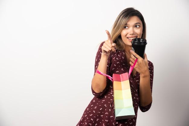 Młoda kobieta trzyma małą torbę sklepową i filiżankę napoju na białej ścianie.