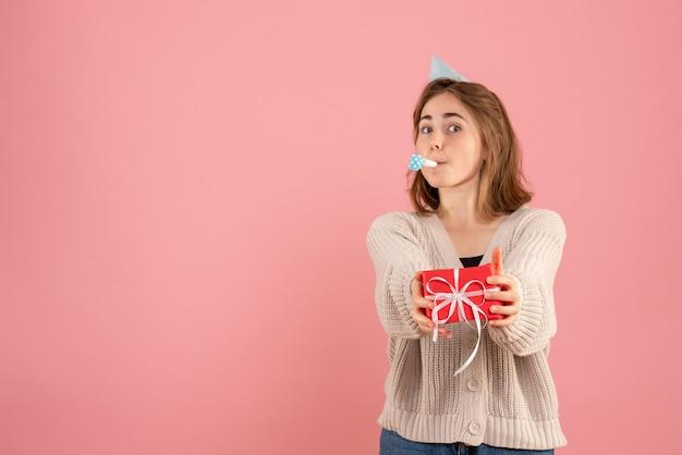 Młoda kobieta trzyma małe prezenty świąteczne na różowo