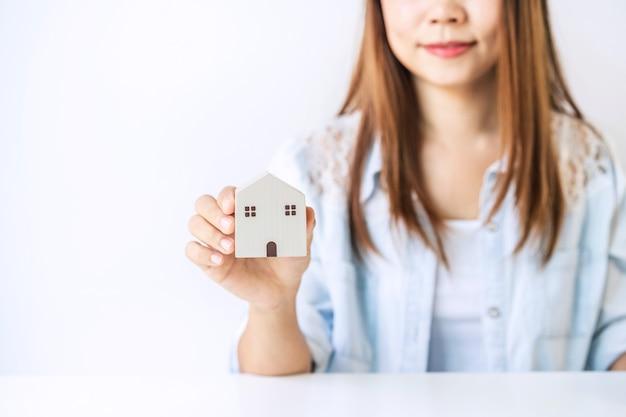 Młoda kobieta trzyma mały domek
