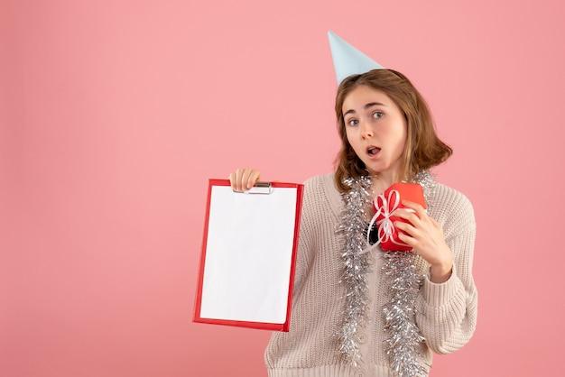 Młoda kobieta trzyma mały prezent świąteczny i uwaga na różowo