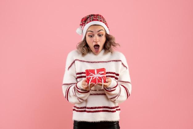 Młoda kobieta trzyma mały świąteczny prezent na różowo