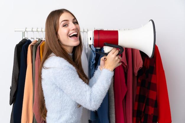 Młoda kobieta trzyma megafon w sklepie odzieżowym