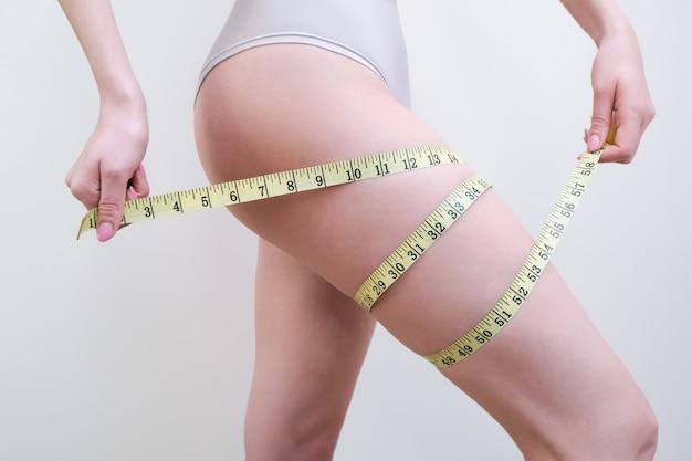 Młoda kobieta trzyma miarkę na jasnym tle. koncepcja problemu cellulitu