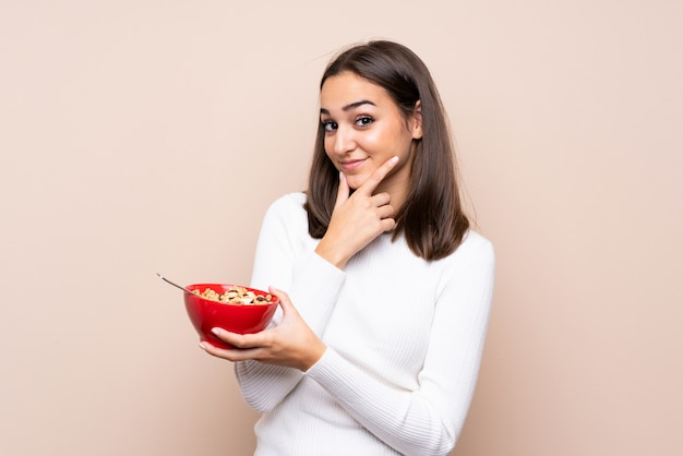 Młoda kobieta trzyma miskę zbóż i myślenia