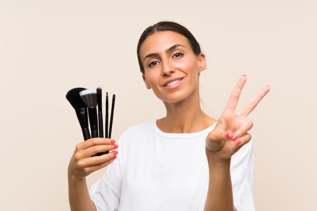Młoda kobieta trzyma mnóstwo makeup muśnięcie uśmiecha się zwycięstwo znaka i pokazuje