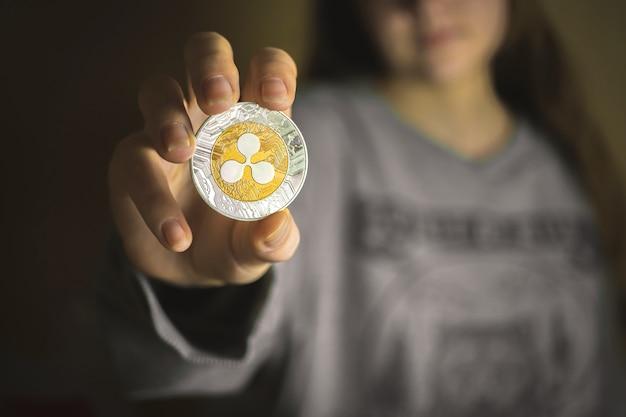 Młoda kobieta trzyma monetę ripple, zdjęcie tła biznesowego kryptowaluty