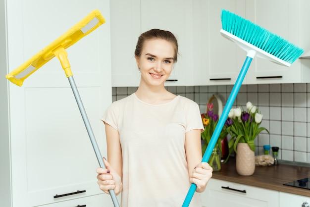 Młoda kobieta trzyma mopy. kobieta jest gotowa do sprzątania domu. gospodyni sprzątająca dom