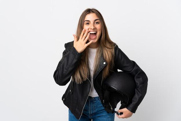 Młoda kobieta trzyma motocyklowego hełm nad biel ścianą z niespodzianka wyrazem twarzy
