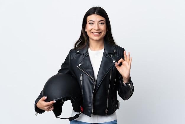 Młoda kobieta trzyma motocyklowego hełm nad odosobnioną biel ścianą pokazuje ok znaka z palcami