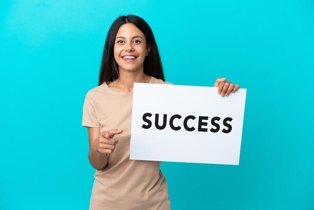 Młoda kobieta trzyma na białym tle afisz z tekstem sukces i wskazuje do przodu