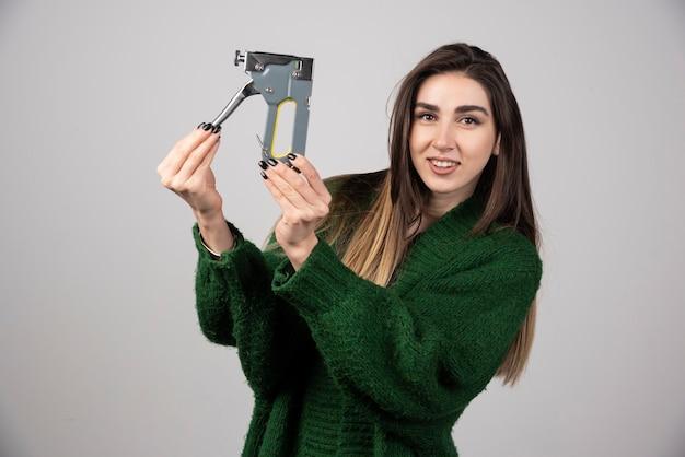 Młoda kobieta trzyma narzędzie pracy na szarym tle.