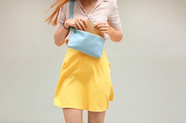 Młoda kobieta trzyma niebieską skórzaną sprzęgło na świetle