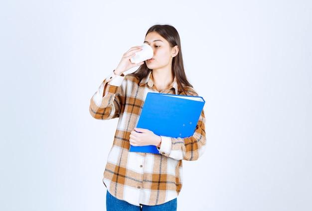 Młoda kobieta trzyma niebieski folder i pije filiżankę kawy.