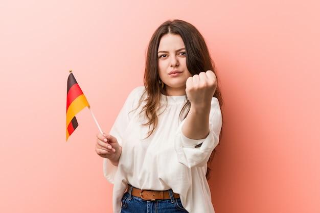 Młoda kobieta trzyma niemcy flaga pokazuje pięść kamera, agresywny wyraz twarzy.
