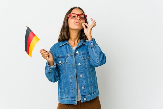 Młoda kobieta trzyma niemiecką flagę na białym tle na białej ścianie z palcami na ustach, zachowując tajemnicę