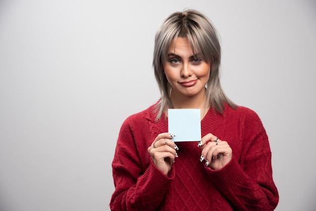 Młoda kobieta trzyma notatnik na szarym tle.