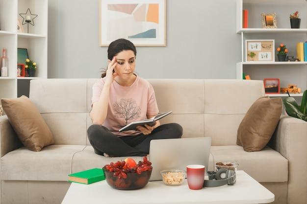 Młoda kobieta trzyma notebook siedząc na kanapie za stolikiem kawowym, patrząc na laptopa w salonie