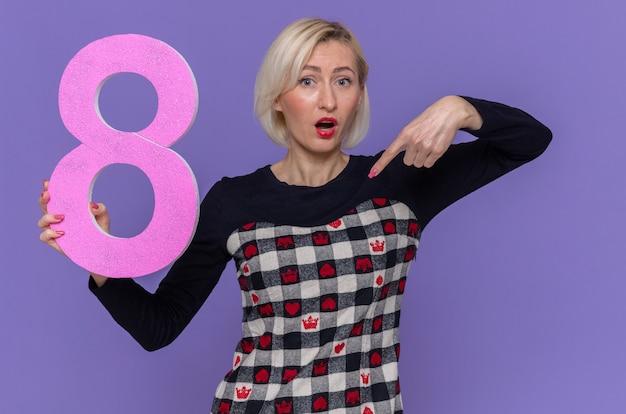 Młoda kobieta trzyma numer osiem