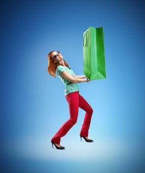 Młoda kobieta trzyma ogromną torbę na zakupy na niebieskim tle