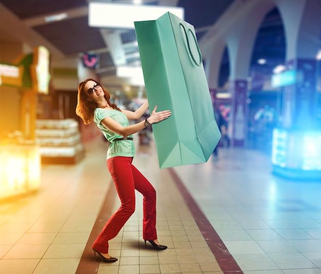 Młoda kobieta trzyma ogromną torbę na zakupy w centrum handlowym