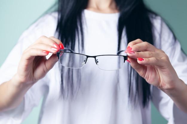 Młoda kobieta trzyma okulary optyczne