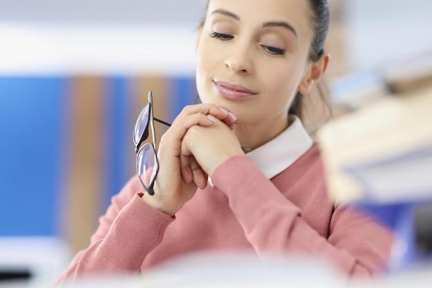 Młoda kobieta trzyma okulary w dłoniach w przerwie biurowej w koncepcji pracy
