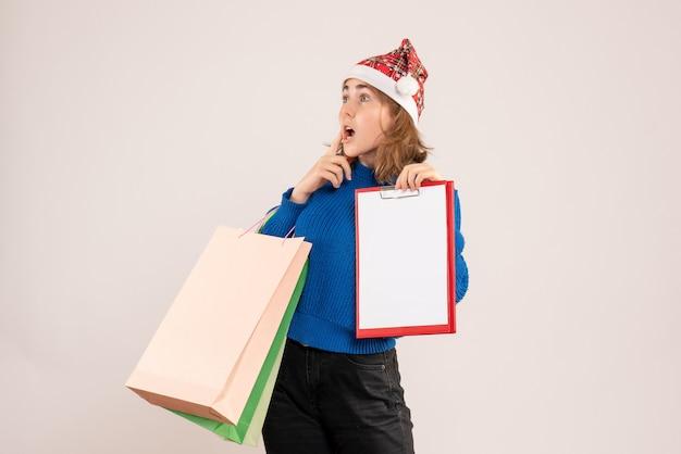 Młoda kobieta trzyma opakowania na zakupy i uwaga na białym tle