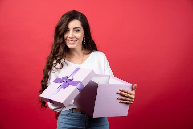 Młoda kobieta trzyma otwarty prezent na czerwonym tle. zdjęcie wysokiej jakości
