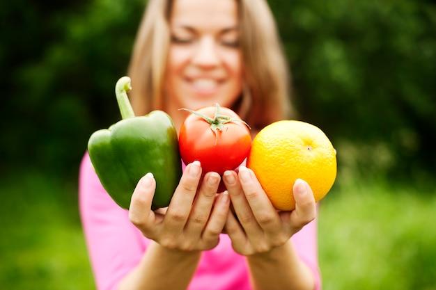Młoda kobieta trzyma owoce i warzywa