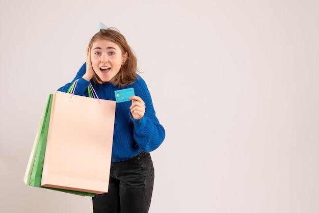 Młoda kobieta trzyma pakiety zakupów i karta bankowa na białym tle