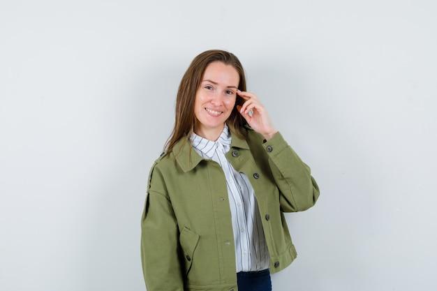 Młoda kobieta trzyma palce na skroniach w koszulę, kurtkę i wyglądam pewnie. przedni widok.