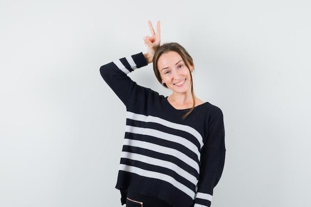 Młoda kobieta trzyma palce nad głową jak uszy królika w dzianinie w paski i czarne spodnie i wygląda na szczęśliwą