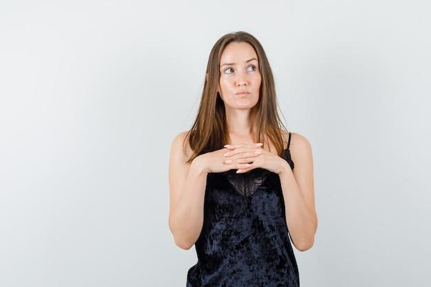 Młoda kobieta trzyma palce splecione, patrząc w czarny podkoszulek i patrząc poważnie.