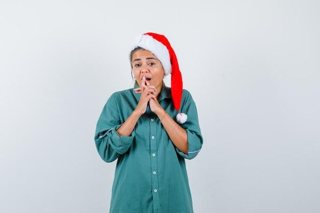 Młoda kobieta trzyma palce splecione w koszulę, kapelusz santa i patrząc w szoku. przedni widok.