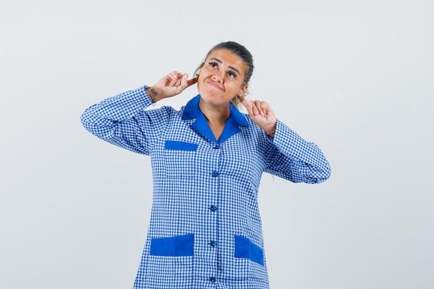 Młoda kobieta trzyma palce wskazujące za uchem w niebieskiej koszuli piżamy w kratkę i wygląda ładnie, widok z przodu.