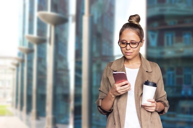 Młoda kobieta trzyma papierowy kubek kawy patrząc na ekran telefonu komórkowego w pobliżu centrum biznesowego