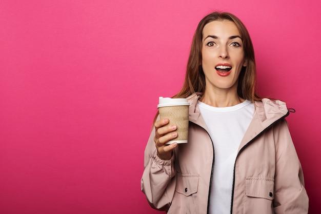 Młoda kobieta trzyma papierowy kubek z kawą z zdziwioną twarzą