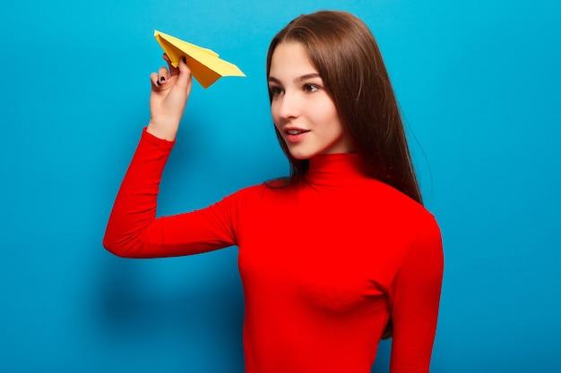 Młoda kobieta trzyma papierowy samolot