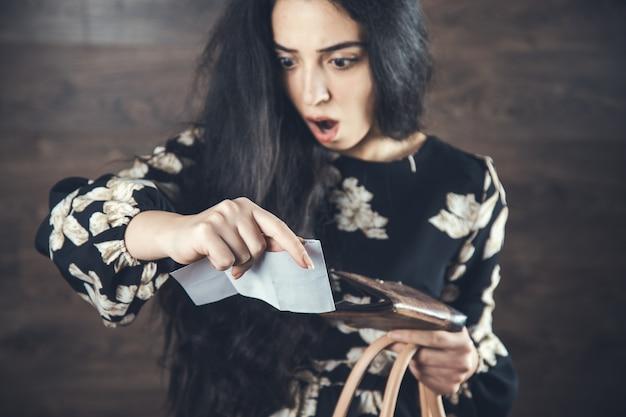 Młoda kobieta trzyma paragon i portfel
