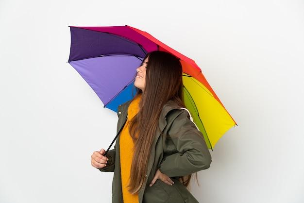 Młoda kobieta trzyma parasol na białym tle cierpi na bóle pleców za to, że podjęła wysiłek