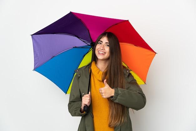 Młoda kobieta trzyma parasol na białym tle na białej ścianie, dając gest kciuki do góry
