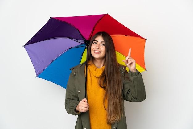 Młoda kobieta trzyma parasol na białym tle na białej ścianie i podnosi palec na znak najlepszych