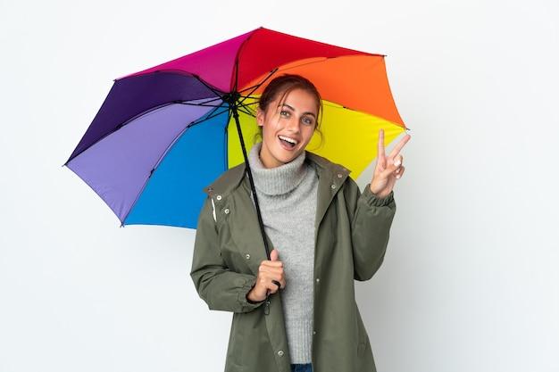 Młoda kobieta trzyma parasol na białym tle na białej ścianie i uśmiecha się i pokazuje znak zwycięstwa