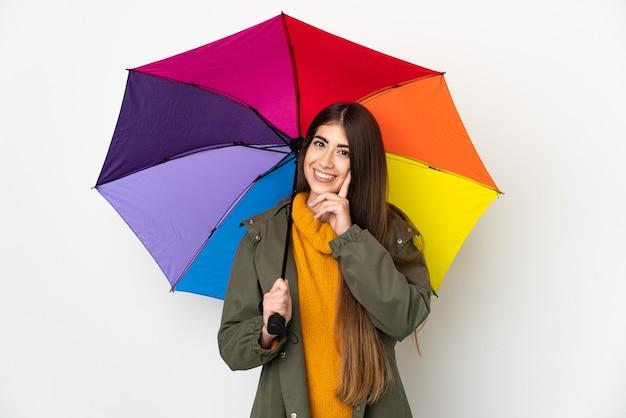 Młoda kobieta trzyma parasol na białym tle na białej ścianie myśli pomysł, patrząc w górę