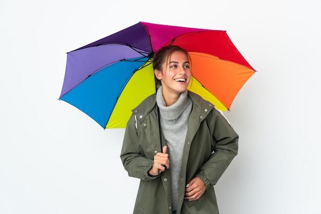 Młoda kobieta trzyma parasol na białym tle na białej ścianie pozowanie z rękami na biodrze i uśmiechnięty