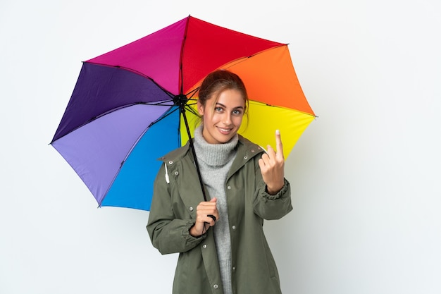 Młoda kobieta trzyma parasol na białym tle na białej ścianie robi nadchodzący gest