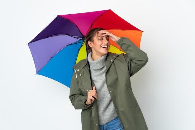 Młoda kobieta trzyma parasol na białym tle na białej ścianie uśmiecha się dużo