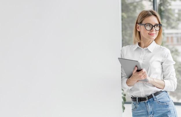 Młoda kobieta trzyma pastylkę z kopii przestrzenią